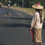 Flaggirl controlling traffic at the road construction near Bago in Myanmar